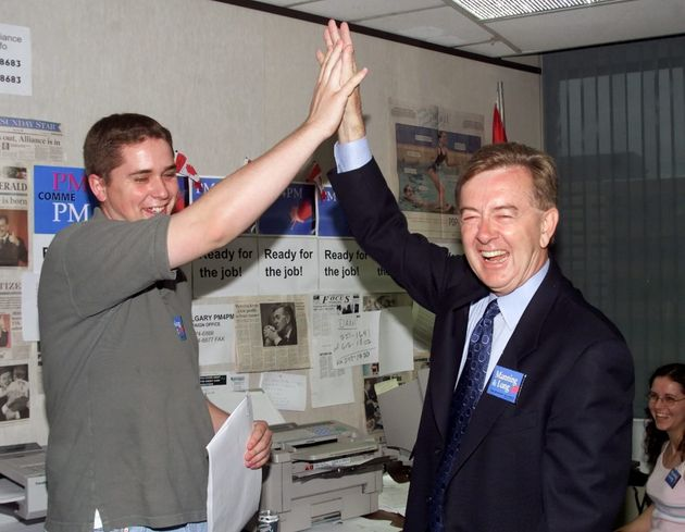 Canadian Alliance candidate Preston Manning gives a high five to Andrew Scheer of the University of Ottawa...