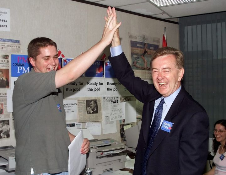 Canadian Alliance candidate Preston Manning gives a high five to Andrew Scheer of the University of Ottawa Canadian Alliance Club during a stop in the Manning campaign headquaters in Ottawa on July 3, 2000.