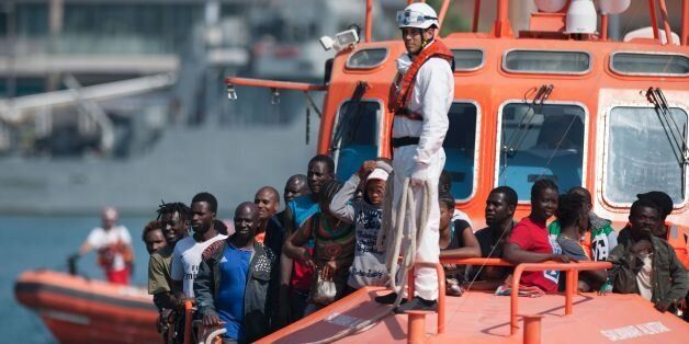 A group of migrants arrive on a Spanish coast guard vessel into the southern Spanish port of Malaga on...