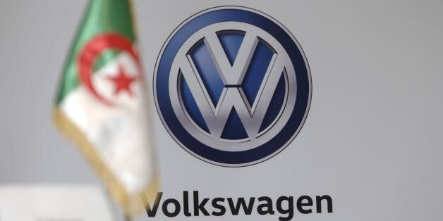 The Algerian national flag is seen in front of a German carmaker Volkswagen (VW) logo during a meeting...