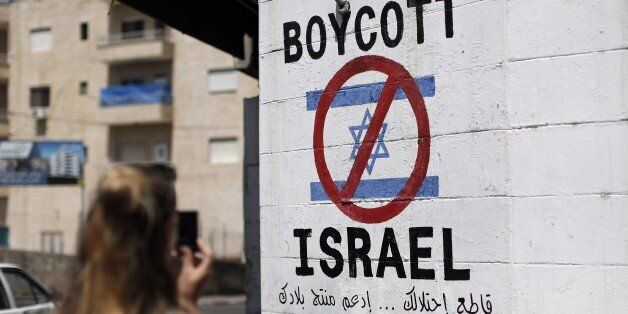 A tourist photographs a sign painted on a wall in the West Bank biblical town of Bethlehem on June 5,...