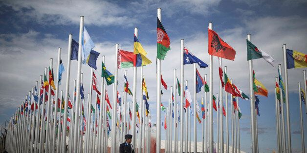 A member of Moroccan security stands guard next to flags of participating UN member states, on the entrance...