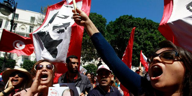 A demonstrator (L) holds a portrait of the late Tunisian opposition leader Chokri Belaid as others wave...
