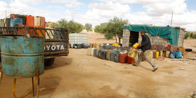 A man fills containers with gasoline at the southern Libya-Tunisia border crossing in Dehiba, April 17,...