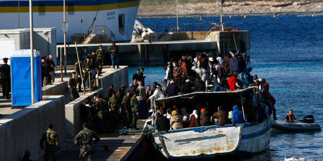 A wooden boat packed with African immigrants, fleeing the unrest in Libya, berths at a jetty in Cirkewwa...