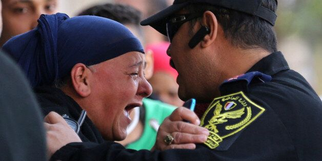 A relative of one of the blast victims screams at a police officer in front of St. Mark's Coptic Orthodox...