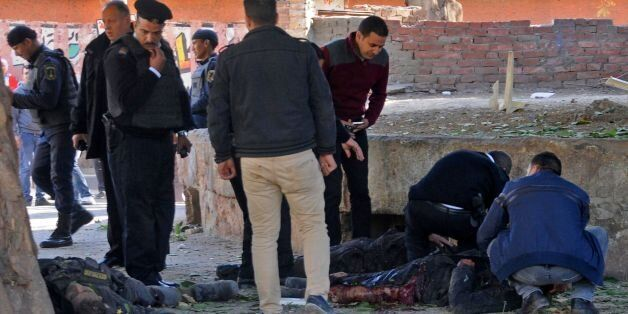 EDITORS NOTE: Graphic content / Egyptians check bodies at the site of a bomb attack next to a police...