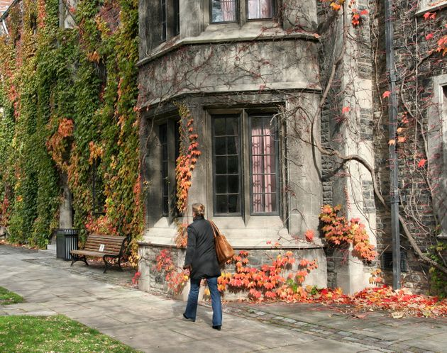 An students walks past an old college building at the University of