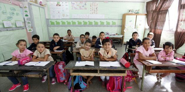 Students cross their arms to demonstrate they are listening carefully to their teacher at Al Hakim El...