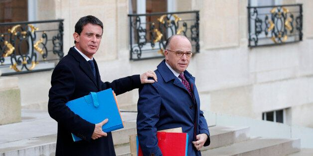 French Prime Minister Manuel Valls (L) and Interior Minister Bernard Cazeneuve leave the weekly cabinet...