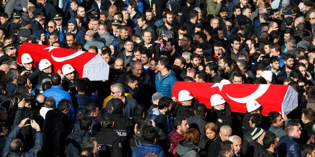 People carry the flag-draped coffins of police officers killed in Saturday's blasts in Istanbul, Turkey,...