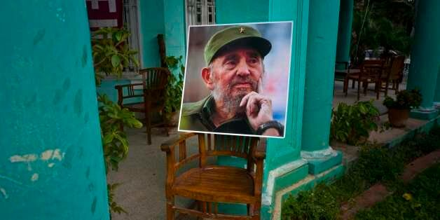 An image of the late Fidel Castro stands on a chair in a government building in Havana, Cuba, Sunday,...