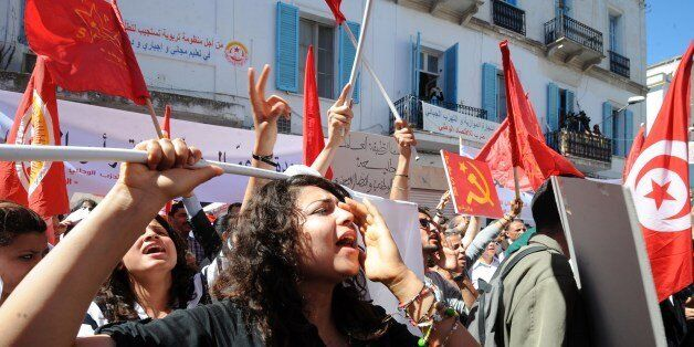 Tunisian workers from UGTT Tunisian General Labour Union shout slogans as they attend a May Day rally...