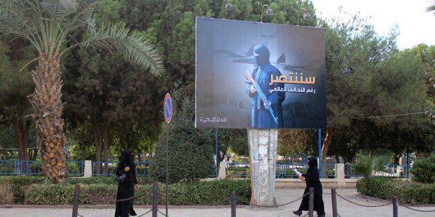 Des femmes en niqab marche sous un panneau érigé par le groupe de l'Etat islamique (Daech) dans le cadre...