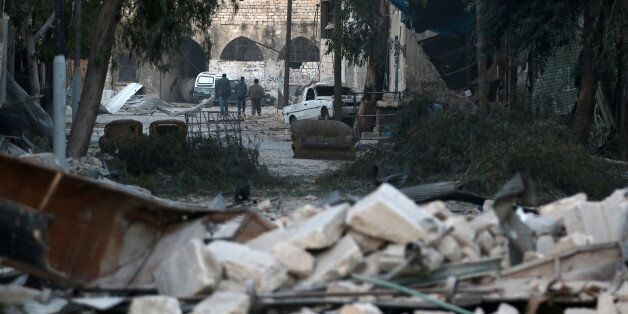 People walk near rubble of damaged buildings, in the rebel-held besieged area of Aleppo, Syria November...