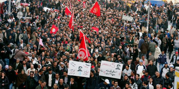 Trade unionists shouts slogans as they rally outside the headquarters of the Union of Tunisian Workers...