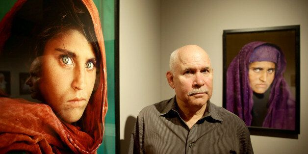 US photographer Steve McCurry poses next to his photos of the 'Afghan Girl' named Sharbat Gula at the...