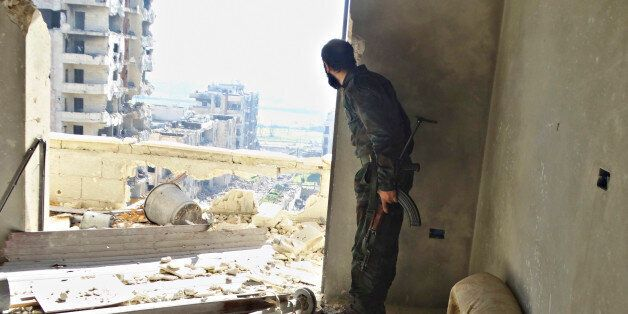 A rebel fighter stands with his weapon inside a damaged building in the northwestern Homs district of...