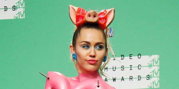 Miley Cyrus poses backstage after hosting the 2015 MTV Video Music Awards in Los Angeles, California,...