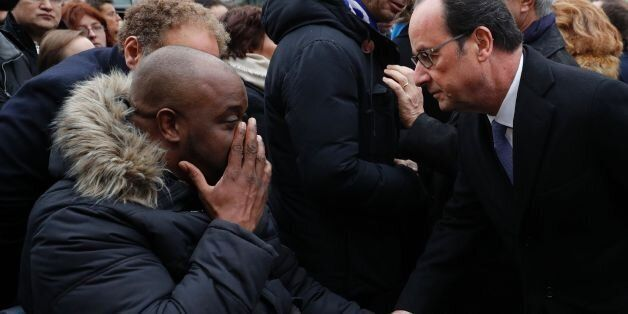 French President Francois Hollande (R) speaks with a victim after unveiling a commemorative plaque outside...