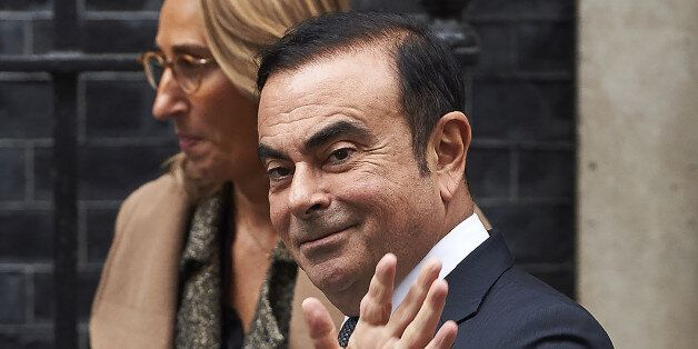 Nissan CEO Carlos Ghosn (R) waves as he leaves No 10 Downing Street in central London on October 14,...