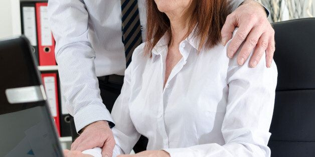 Manager putting his hand on the shoulder of his secretary, at the
