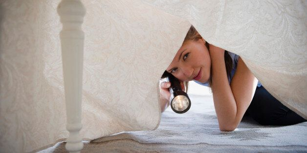 USA, New Jersey, Jersey City, Woman with flashlight looking under