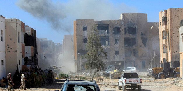 Smoke rises as fighters of Libyan forces allied with the U.N.-backed government gather at the eastern...