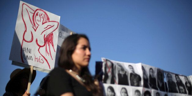 Activists take part in a march to protest violence against women and the murder of a 16-year-old girl...