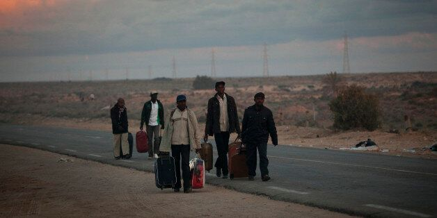 Men from Ghana, who used to work in Libya and fled the unrest in the country, carry their belongings...