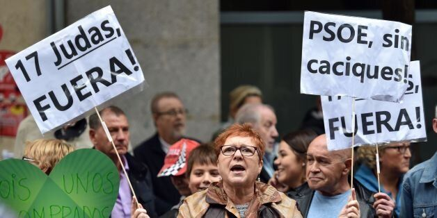 A PSOE supporter holds placards reading '17 Judas out' 'PSOE without chiefs' outside the Spanish Socialist...
