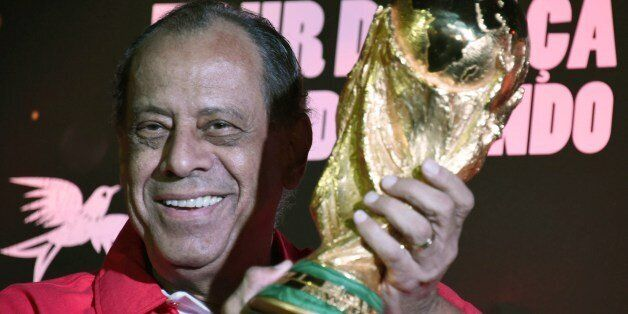 Carlos Alberto, former captain of the Brazilian 1970's football team, holds the World Cup which has just...