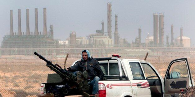 FILE - In this March 5, 2011 file photo, an anti-government rebel sits with an anti-aircraft weapon in...