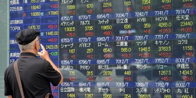 An investor watches a share prices board in Tokyo on September 9, 2015. Japan's share prices rose nearly...