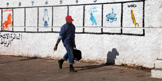 A man walks past a wall marked by the numbers of districts where civilians should go to vote, in Rabat...
