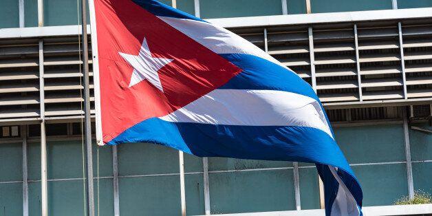 HAVANA CITY, HAVANA, CUBA - 2015/09/19: Cuban flag in pole with building design in the background.The...