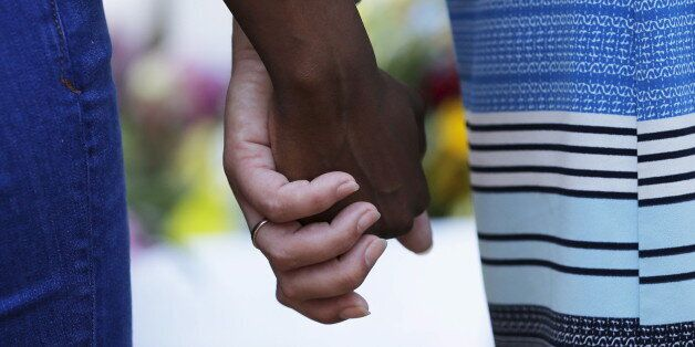 Mourners hold hands outside the Emanuel African Methodist Episcopal Church in Charleston, South Carolina,...