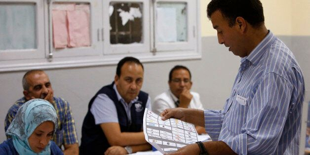 The president of a polling station checks a ballot as officials and political party's representatives...
