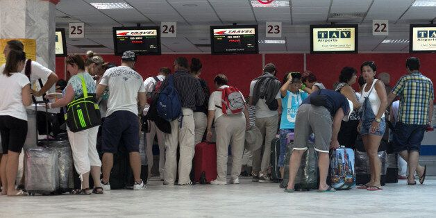 Tourists line up at Monastir airport as they prepare to leave Tunisia, a day after a shooting attack...