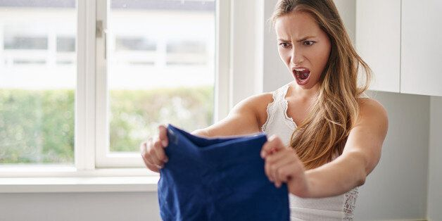 Cropped shot of a young woman reacting angrily to the fact her shorts shrunk in the