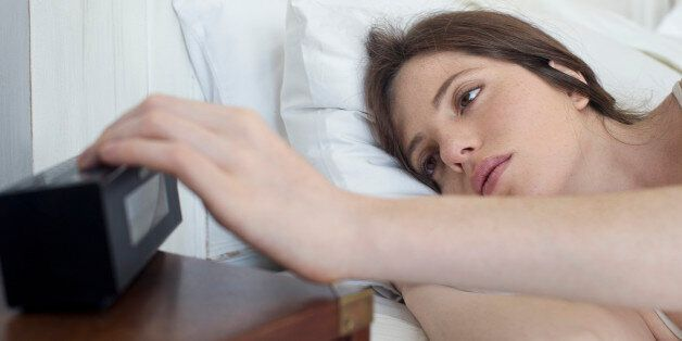 Woman in bed pressing alarm clock snooze
