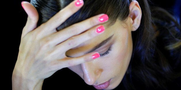 A model lets her nail polish dry before the Blumarine fashion show during Milan Fashion Week Spring/Summer...