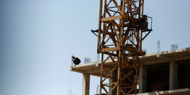 A worker looks down from the top of a new apartment building being built at a construction site in Algiers,...