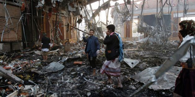 Yemeni rescue workers search for victims amid the rubble of a destroyed building following reported airstrikes...