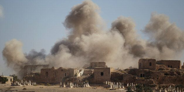 Smoke rises behind the ancient castle of the rebel-controlled town of Maaret al-Numan after airstrikes...