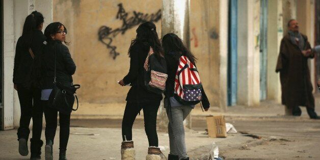 Students walk to their houses at the impoverished Zhor neighborhood of Kasserine, where young people...