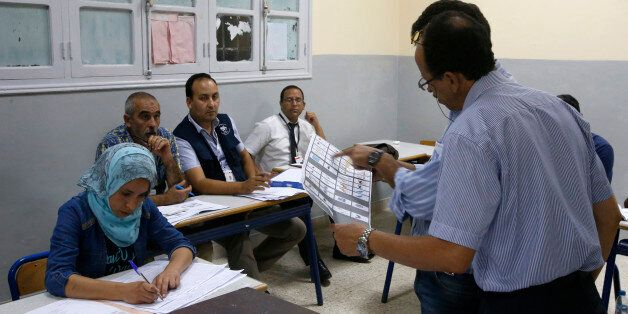 The president of a polling station shows a ballot as officials and political party's representatives...