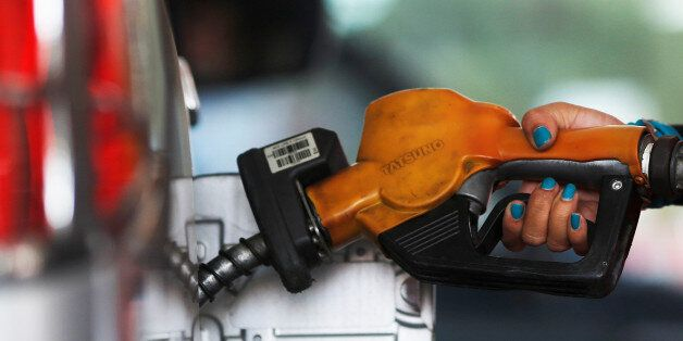 A worker at state-owned Pertamina, the country's main retailer of subsidised fuel, fills a vehicle at...