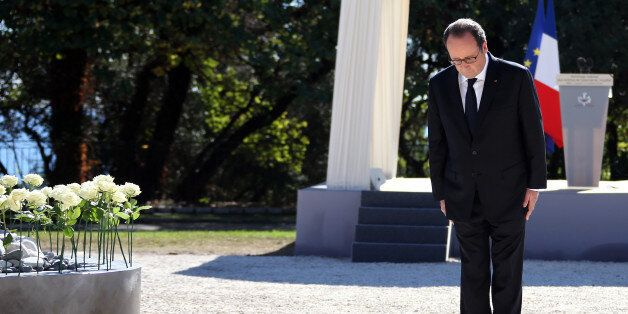 French President Francois Hollande bows as he pays his respects to the families of victims as he attends...