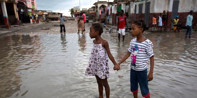 Girls hold hands as they help each other wade through a flooded street after the passing of Hurricane...